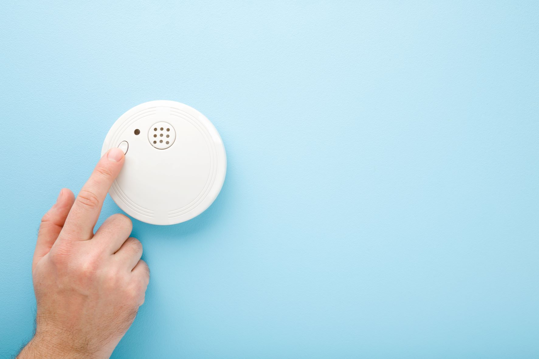 Person pressing test button on fire, smoke, and gas detector alarm